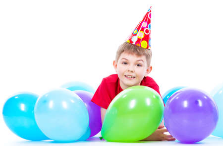 children birthday: Happy smiling boy in red t-shirt lying on the floor with colorful balloons - isolated on a white.