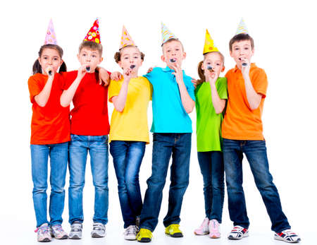 birthday hat: Group of happy children in colored t-shirts with party blowers - isolated on a white background.