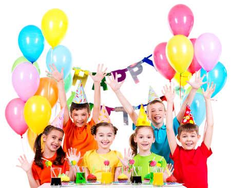 カラフルなシャツ、白で隔離 - 上げられた両手の誕生日パーティーでの子供たちのグループです。