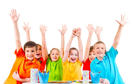 niños sentados: Group of children in colored t-shirts sitting at a table with raised hands.