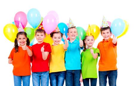 色の t シャツや白い背景の上のサインを親指を示すバルーン パーティー帽子の幸せな子供たちのグループです。 写真素材