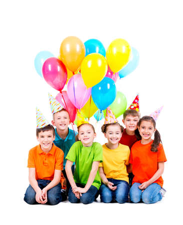 children party: Happy boys and girls in party hat with colored balloons sitting on the floor - isolated on white. LANG_EVOIMAGES