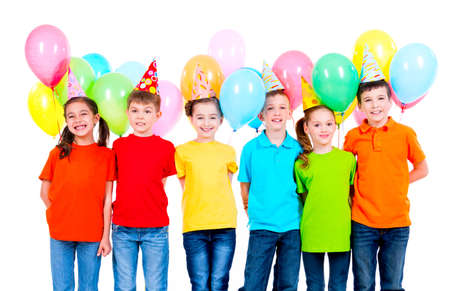 Group of smiling children in colored t-shirts and party hats with balloons on a white background. LANG_EVOIMAGES