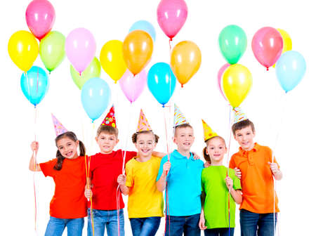 hubcap: Group of smiling children in colored t-shirts and party hats with balloons on a white background. LANG_EVOIMAGES