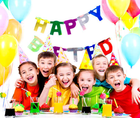 Group of laughing kids having fun at the birthday party - isolated on a white. Standard-Bild