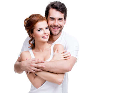 happy couple: Portrait of beautiful smiling couple posing at studio over white background.