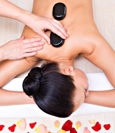 hot stones: Beautiful woman relaxing in spa salon with hot stones on body. Beauty treatment therapy Stock Photo