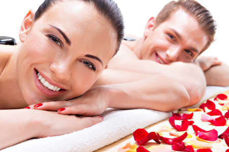 salon and spa: Portrait of happy smiling couple relaxing in spa salon with hot stones on body. Stock Photo
