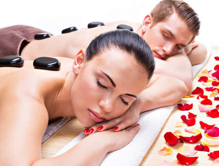 couple: Portrait of attractive couple relaxing in spa salon with hot stones on body.