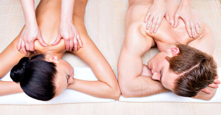 massages: Portrait of beautiful couple lying  in a spa salon enjoying a deep tissue back massage together. Stock Photo