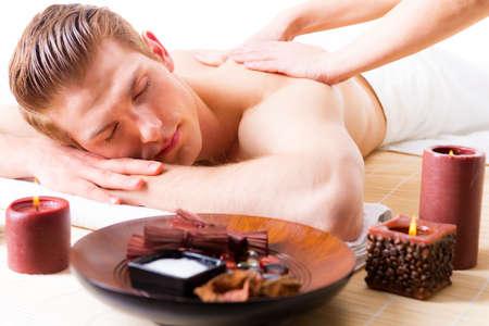 salon and spa: Handsome man lying in a spa salon enjoying a deep tissue back massage.