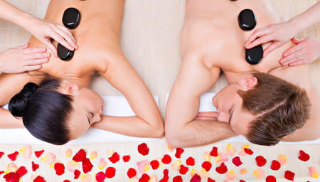 hot stones: Beautiful couple relaxing in spa salon with hot stones on body. Beauty treatment therapy.