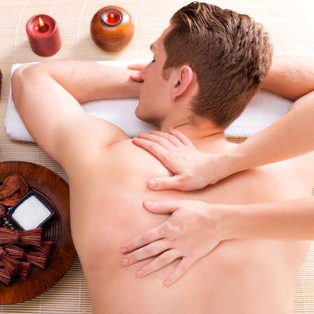 Pohledný muž uvolněně a těší hluboké tkáně masáž zad v lázeňském salonu. Reklamní fotografie