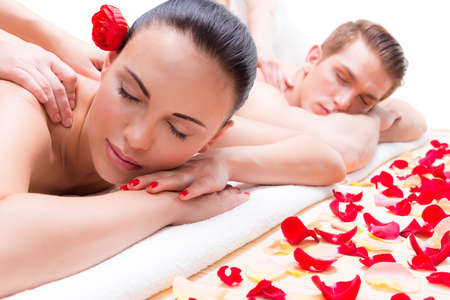 roses petals: Attractive couple lying  in a spa salon enjoying a deep tissue back massage together.