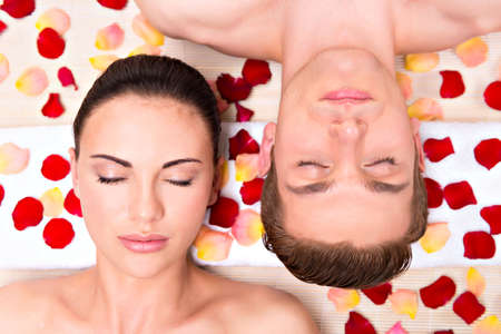 masaje: Hermosa joven pareja se relaja situada en pétalos de rosa.