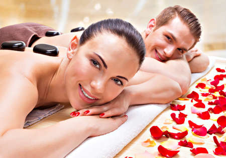 red rose bokeh: Portrait of happy smiling couple relaxing in spa salon with hot stones on body. Stock Photo