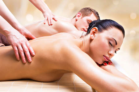 Beautiful couple lying  in a spa salon enjoying a deep tissue back massage together.