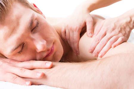 homme massage: Bel homme couché dans un salon de spa bénéficiant d'un massage du dos des tissus profonds.