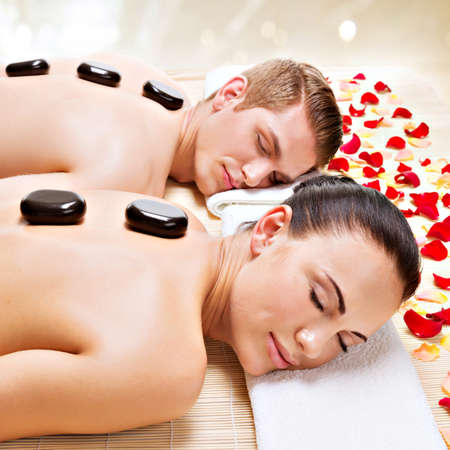 Portrait of attractive couple relaxing in spa salon with hot stones on body.