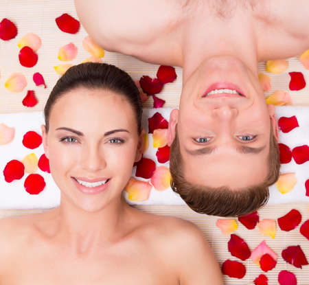 spa woman: Beautiful young couple relaxes lying in rose petals.
