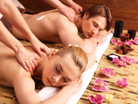 adult massage: Attractive couple lying  in a spa salon enjoying a deep tissue back massage together.