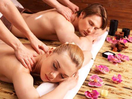 massaggio: Coppia attraente che si trova in un salone di spa che gode di un tessuto profondo massaggio alla schiena insieme.