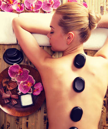 Mooie vrouw die in spa salon met hete stenen op het lichaam. Schoonheidsbehandeling therapie