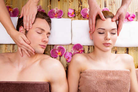 male massage: Beautiful couple lying in a spa salon enjoying head massage together.