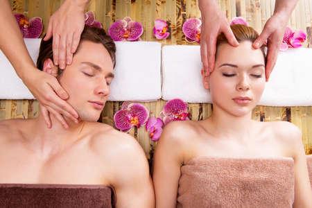 homme massage: Belle couple allongé dans un salon de spa en profitant massage de la tête ensemble.