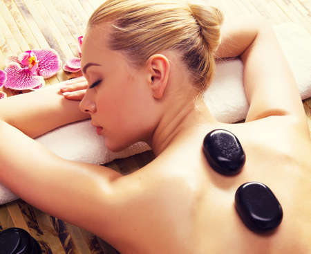 hot stones: Beautiful woman relaxing in spa salon with hot stones on body. Beauty treatment therapy LANG_EVOIMAGES