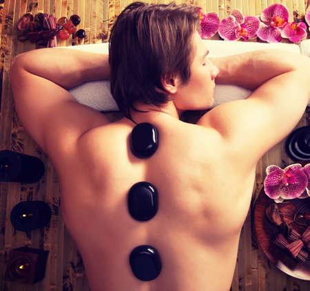 homme massage: Bel homme ayant massage aux pierres dans le spa salon. Mode de vie sain.