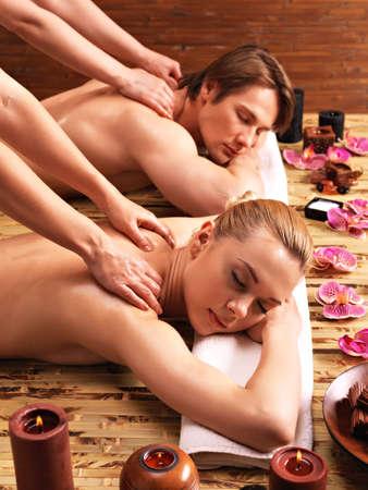 Atraktivní pár ležící v lázeňském salonu těší hluboké tkáně masáž zad dohromady. LANG_EVOIMAGES