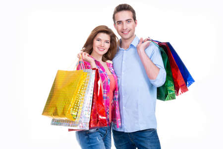 playfulness: Portrait of beautiful young happy couple with colored shopping bags - isolated on white.