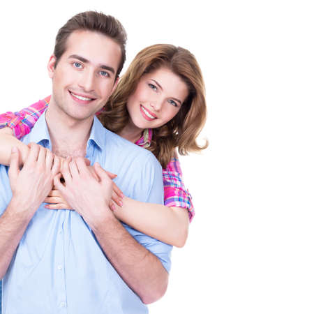 playfulness: Portrait of young happy attractive couple standing in studio isolated on white background.