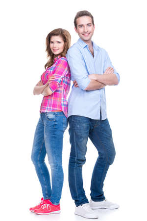 family isolated: Full portrait of smiling couple standing back to back isolated on white background. Stock Photo