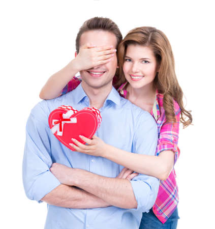 playfulness: Portrait of beautiful happy couple isolated on white background. Attractive women make a surprise to man.