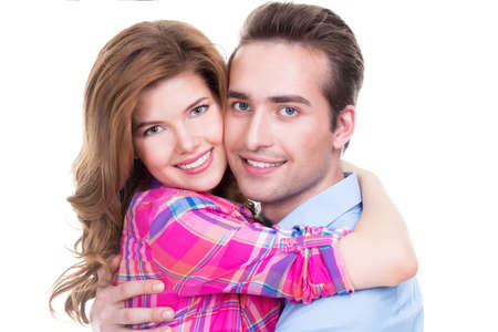 playfulness: Cheerful beautiful couple in embrace looking at camera on white background.