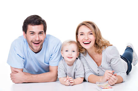 family isolated: Photo of the smiling young parents with little child lying on the floor - isolated on white background.