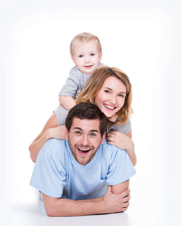 �aucasian: Photo of the smiling young parents with little child lying on the floor - isolated on white background.
