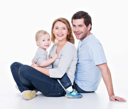 familie: Foto van de gelukkige jonge gezin met kind zittend op de vloer - geïsoleerd op een witte achtergrond. Stockfoto