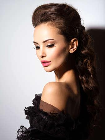 schöne frauen: Schönes Gesicht einer jungen Frau in sexy schwarzen Kleid posiert im Studio auf weißem Hintergrund