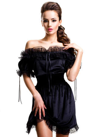 glamour woman elegant: Young sexy woman in black dress posing at studio on white background