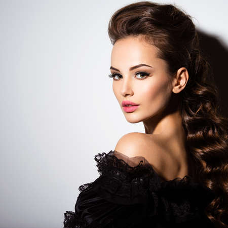 白い背景のスタジオでポーズを黒のドレスでセクシーな女性の美しい顔