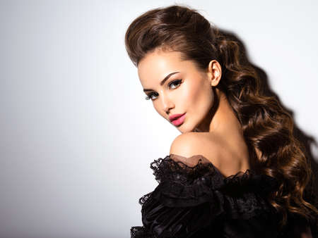 donne eleganti: Bel volto di una giovane donna sexy in abito nero in posa in studio su sfondo bianco