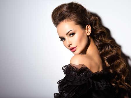 mujeres elegantes: Hermoso rostro de una mujer atractiva joven en vestido negro posando en el estudio sobre fondo blanco LANG_EVOIMAGES