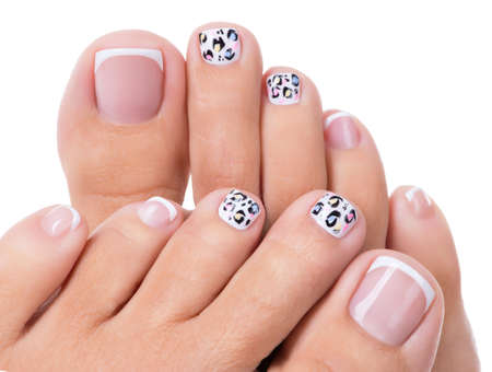 pedicure: Beautiful womans nails of legs with beautiful french manicure and art design Stock Photo