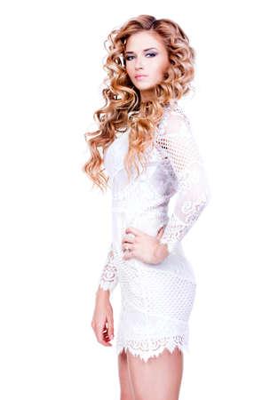 cabello rubio: Retrato de mujer sexy con el pelo largo y rizado rubia en vestido blanco posando en el estudio sobre bakground blanco.