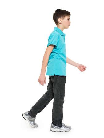 파란색 티셔츠 캐주얼에 대 소년을 걷는 전체 세로 흰색 배경에 고립입니다.