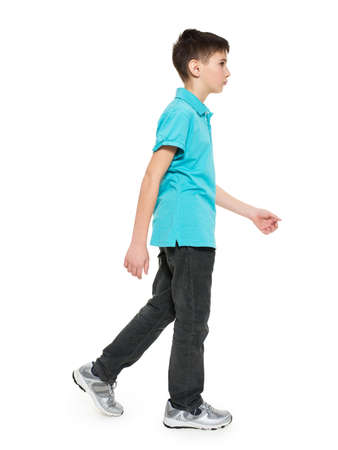 from side: Full portrait of walking teen boy in blue t-shirt casuals  isolated on white background.