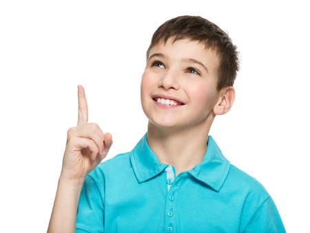 pointing finger up: Portrait of the cheerful teen boy pointing finger up -  isolated over white background